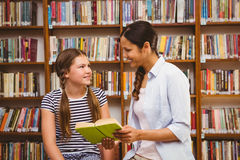 Teacher and girl reading book in library Royalty Free Stock Photography