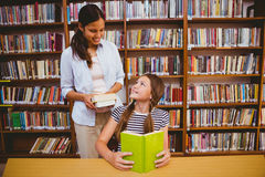 Teacher and girl reading book in library Stock Images