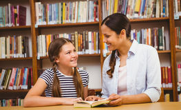 Teacher and girl reading book in library Stock Photo