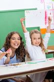 Teacher With Girl Showing Drawing At Desk Stock Images