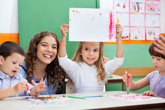 Teacher With Girl Showing Drawing At Desk Stock Photos