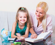 Teacher and girl studying at home Stock Images