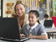Teacher And Girl Using Laptop In Class stock photography