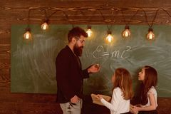 Teacher and girls pupils in classroom near chalkboard. Man with beard in formal suit teaches schoolgirls physics stock photo