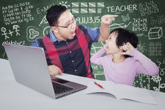 Teacher gives order on his student for doing assignment. Young male teacher shouting and pointing his student while giving order for doing school assignment Royalty Free Stock Photo