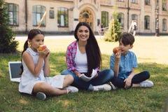 Teacher giving apple to kid stock photo