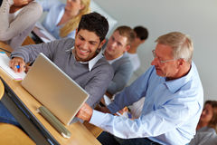 Teacher giving assistance in class. Elderly teacher giving assistance in university class royalty free stock photography