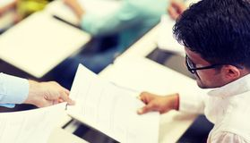 Teacher giving exam test to student at lecture royalty free stock photography