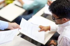 Teacher giving exam test to student at lecture Royalty Free Stock Image