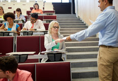 Teacher giving exam tests to students at lecture Stock Images
