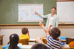 Teacher giving a geography lesson in classroom. At the elementary school royalty free stock image