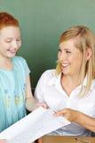 Teacher giving girl test back Royalty Free Stock Photo