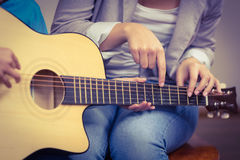 Teacher giving guitar lessons to pupil Stock Images