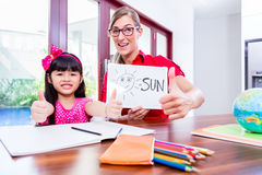 Teacher giving language lessons to Chinese child Stock Photography