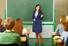 Teacher giving a lecture. Good looking teacher explaning material to her students at the school board royalty free stock image