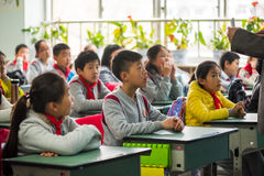 Teacher giving a lesson to children in a chinese classroom. Chengdu, Sichuan Province, China - March 31, 2017: Teacher giving a lesson to children in a chinese Royalty Free Stock Image