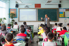 Teacher giving a lesson to children in a chinese classroom. Chengdu, Sichuan Province, China - March 31, 2017: Teacher giving a lesson to children in a chinese Stock Images