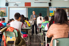 Teacher giving a lesson to children in a chinese classroom. Chengdu, Sichuan Province, China - March 31, 2017: Teacher giving a lesson to children in a chinese Stock Image
