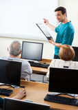 Teacher Giving Lessons To Senior Students In Compute Lab. Young male tutor giving lessons to senior students in compute lab Royalty Free Stock Photos