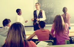 Teacher giving a math lesson. Mature positive teacher giving a math lesson in front of a group of students in the school royalty free stock images
