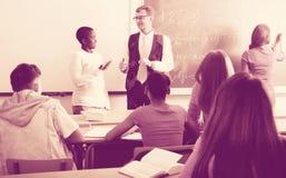 Teacher giving a math lesson. Positive teacher giving a math lesson in front of a group of students in the school stock photography