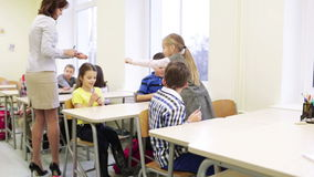 Teacher giving pens to school kids in classroom. Education, elementary school, learning and people concept - teacher giving pens to group of school kids in stock footage