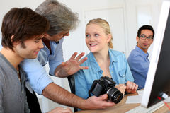 Teacher giving photography tips to students. Teacher in class of photography with students Royalty Free Stock Photos