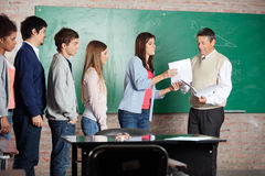 Teacher Giving Test Result To Student At Classroom. Mature male teacher giving test result to student while classmates standing in row at classroom stock photo