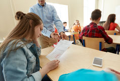 Teacher giving test results to group of students. Education, high school, learning and people concept - upset student girl with bad test result and teacher in stock image