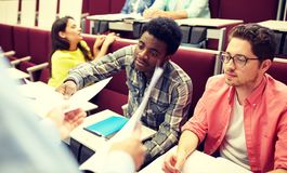 Teacher giving tests to students at lecture stock images
