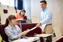 Teacher giving tests to students at lecture Royalty Free Stock Images