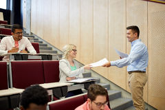 Teacher giving tests to students at lecture Royalty Free Stock Photo