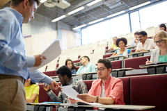 Teacher giving tests to students at lecture royalty free stock photos