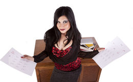 Teacher with graded papers. A teacher is standing in front of her desk holding graded papers royalty free stock image