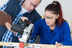 Teacher grading carpentry apprentice Royalty Free Stock Photography
