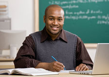Teacher grading papers in school classroom stock images