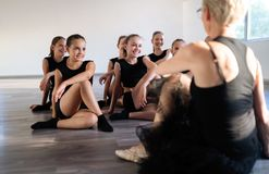 Teacher and group of children exercising dancing and ballet in dance school stock photography
