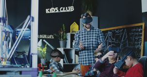 Kids with teacher exploring VR technology. Teacher with group of children having class in school and studying VR technologies in goggles royalty free stock photography