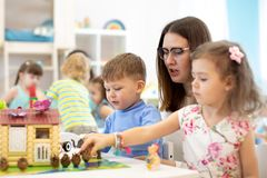 Teacher and group of kids buiding toy house with constructor in craft class. Teacher and group of kids buiding toy house in craft class in preschool. Boy and royalty free stock images