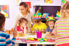 Teacher and group of kids in craft class. Teacher and group of kids in kindergarten class with making handmade crafts stock photos