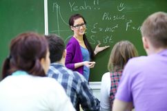 Teacher with group of students in classroom. Young woman-teacher conducts lessons with a group of students stock photo