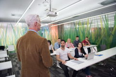 Teacher with a group of students in classroom Stock Image