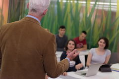 Teacher with a group of students in classroom Stock Photography