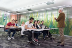 Teacher with a group of students in classroom. Group of students study with professor in modern school classroom Royalty Free Stock Image
