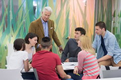 Teacher with a group of students in classroom. Group of students study with professor in modern school classroom Royalty Free Stock Photos