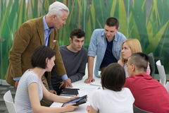 Teacher with a group of students in classroom Stock Photo