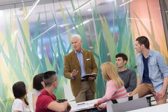 Teacher with a group of students in classroom. Group of students study with professor in modern school classroom Royalty Free Stock Photo
