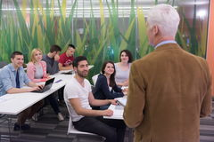 Teacher with a group of students in classroom. Group of students study with professor in modern school classroom Royalty Free Stock Photography