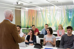 Teacher with a group of students in classroom. Group of students study with professor in modern school classroom Stock Photo