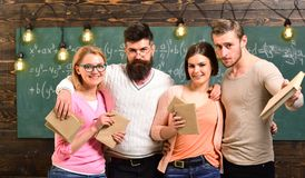 Teacher with group of students, group mates, friends, chalkboard on background. Students hugs with professor, holding. Books in hands. Leisure after classes stock photos